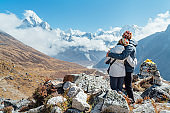 Embracing couple having a rest on Everest Base Camp trekking route near Dughla 4620m. Backpackers left Backpacks, embracing and enjoying valley view with Ama Dablam 6812m peak
