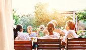 Big multigenerational family has dinner. Summer evening in the garden