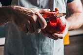 A man with strong hands cuts a pomegranate with a knife