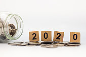 2020 New year, Business, Money, Finance and Saving concept. Closeup of wooden block number with coins in glass jar container and white background with copy space text.