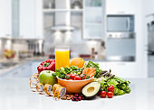 Healthy fresh fruits and vegetables salad in a bowl on kitchen counter
