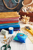 Accessories for quilting and a stack of colorful fabrics for quilting on the background of the box with seashells