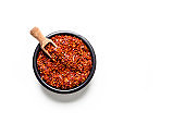 Red chili pepper flakes shot from above on white background