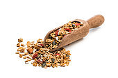 Granola in a wooden serving scoop on white background