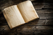 Old open book on rustic wooden table