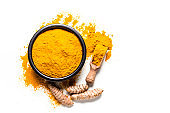 Spices: Turmeric powder and roots shot from above on white background