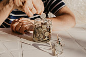 pensioner's hand with savings in the pot