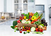 Healthy fresh vegetables in a crate on kitchen counter