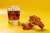 side view fresh deep fried chicken drumstick and wing with cup of iced cola on yellow background