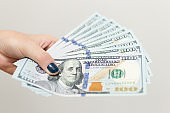 Hand holding cash banknotes of one hundred new us dollars paying bills, payment procedure or bribe, salary
