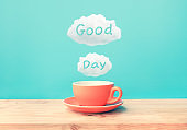 Happy moment with a cup of coffee and good day text on wood bar table background