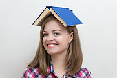 Smiling young caucasian girl woman, reading a book