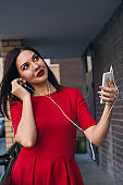young woman with red lipstick in red dress uses phone and earphones