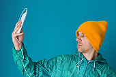young man in a turquoise  sport 90s style jacket and yellow hat holding smartphone with earphones