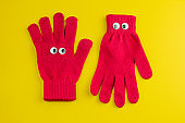 two red gloves isolated on a vibrant yellow background