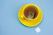 yellow cup of hot tea with tea bag with white mock up label on a blue background