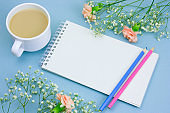 notebook with empty white paper sheet ,colored pencils,coffe with cream cup and floral frame