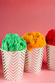 fruit ice cream or frozen yogurt in stripped   cup on a pink background
