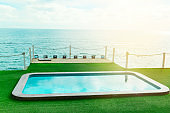 swimming pool by the sea ,summer vacation and luxury living concept