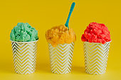 fruit ice cream or frozen yogurt in stripped    cups  with a spoon on a yellow background