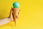female hand holding waffle cone ice cream isolated on a vibrant yellow background