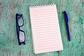 white sheet of paper, blue pen and blue glasses on a mint green shabby wooden background