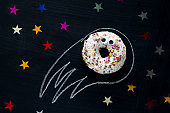 donut meteorite with googly eyes among the stars  on a black chalkboard background