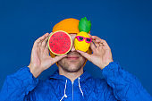 man in a blue sport 90s style jacket and yellow hat  with squishy watermelon and pineapple toys