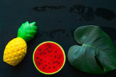monstera green leaf ,pineapple and watermelon squishy toy on blackboard copy space