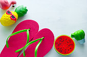 pink beach flip flops  and squishy toy cactus , flamingo,watermelon and pineapple   on white  background