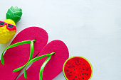 pink beach flip flops  and squishy toy pineapple and watermelon on white  background