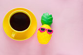 yellow coffee mug and pineapple  squishy toy  on a pink background