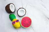 funny pineapple toy in sunglasses,watermelon  and coconut on a marble table