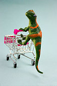 green dinosaur with shopping cart on blue background