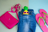 top view flat lay pink bag, blue denim jeans and pink flip flops