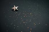blurred dark festive background with golden glitters and metallic star