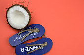 coconut and decorative wooden flip flops on a coral background