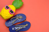 decorative wooden flip flops and squishy toy pineapple on a coral background copy space