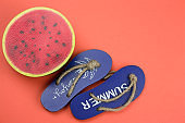 decorative wooden flip flops and squishy toy watermelon  on a coral background copy space