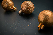 blurred golden metal christmas balls on a black background