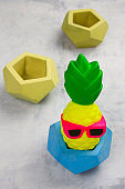 funny pineapple toy in concrete pot