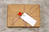 cardboard box with cloth pin with red heart and empty white label
