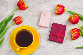gift boxes , coffee cup and tulips on a marble background