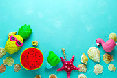vibrant blue  backdrop with sea shells and bright squishy toys frame, top view copy space