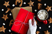 ginger cookies , Santa Claus hand with red gift box and  red mug with marshmallow on a black background