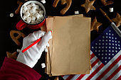 pattern of ginger cookies  and sheets of vintage blank paper with space for text and Santa Claus hand in white glove