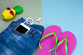 top view flat lay cute pineapple in sunglasses, blue denim jeans , smartphone and pink flip flops