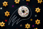 donut meteorite among the stars of cookies on a black chalkboard background, funny children's entertainment with food
