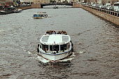 tourists ride on excursion boats on city water channels