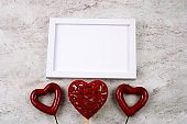 white mock up wooden frame and three red hearts on a marble background